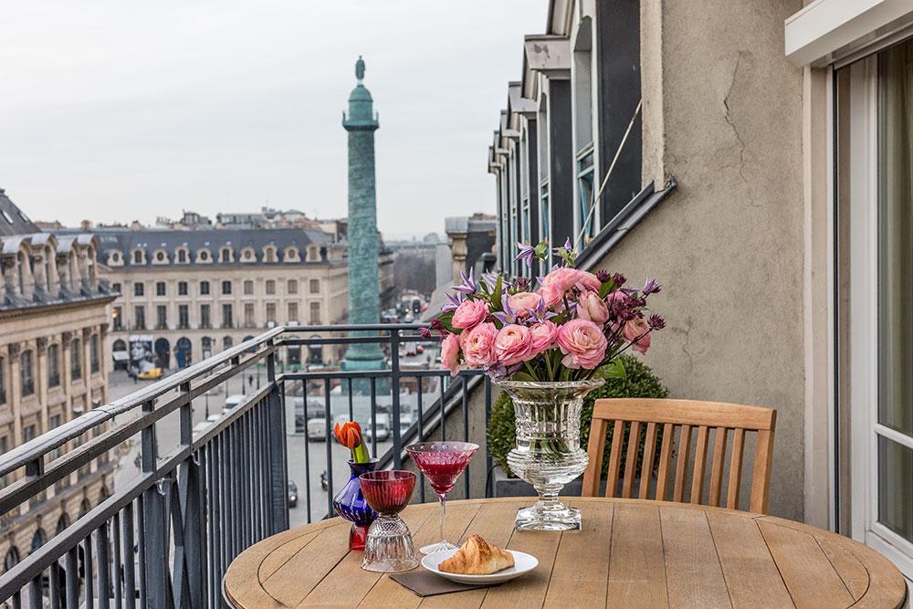 Vue sur la célèbre place Vendôme depuis la terrasse de la suite de l'hôtel Hyatt Paris-Vendôme. Sur la table: collection Les Endiablés par José Lévy pour Saint Louis, vase Quadrille.