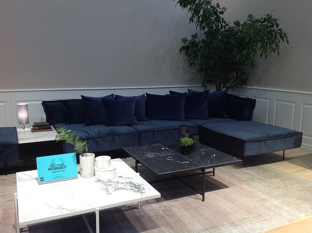 Ambiance plus lumineuse et froide chez Handvärk, mais on retrouve les mêmes éléments; canapé en velours, table en marbre et plante verte.